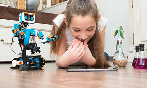 Young girl lying on floor with tablet and toy robot