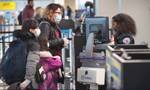 Airline passengers wearing face masks at check-in.