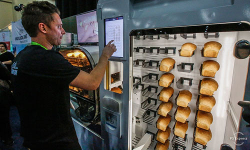 A man pressing buttons on the breadbot, an autonomous bread-making machine that prepares bread without human assistance