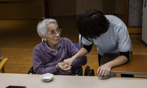 An elderly woman talking to her caretaker