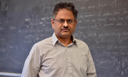 Photo of Professor Jayanti in front of a chalkboard.