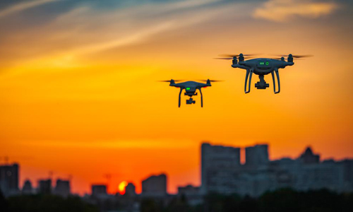 Two drones flying with sunset in background