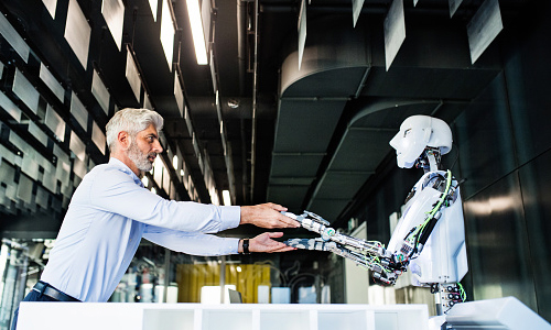 Scientist holding hands of a robot