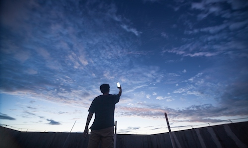 Man pointing smartphone toward the night sky