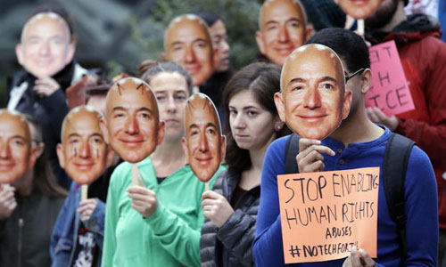 People holding up an image of Jeff Bezos near their faces