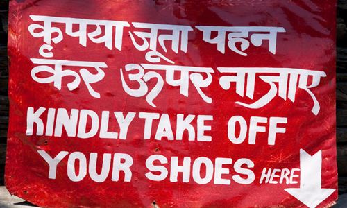 """Sign written in Hindi with English translation """"kindly take off your shoes"""" written below."""