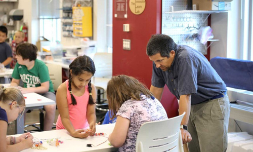 Professor Adam Maltese, working with table of female students at the Make, Innovate, Learn Lab Makerspace.