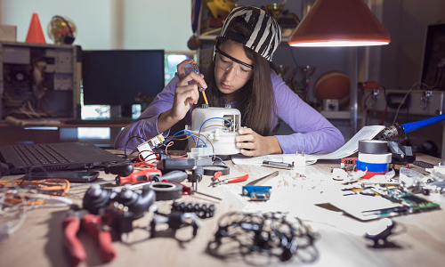 A young girl at a desk completing an engineering project