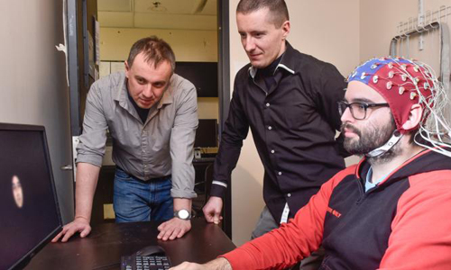 Dan Nemrodov (left) and Professor Adrian Nestor (left)  observing a man using the brain scanning device they developed.