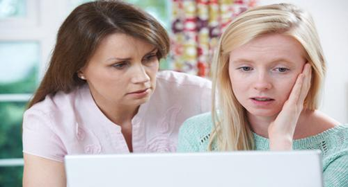 Mom and daughter look at laptop