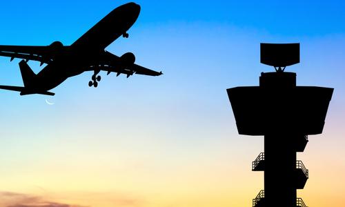 Airplane flies beside an air traffic control tower