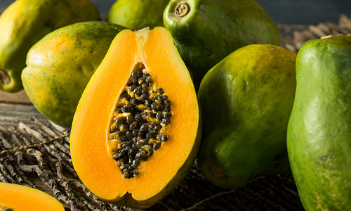 Papayas on a wooden table with one cut in half