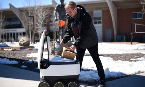 George Mason University student retrieves food from autonomous delivery robot