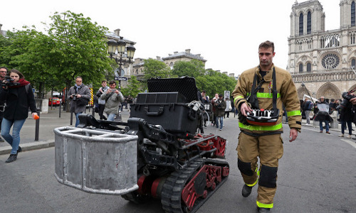 Firefighter with Colossus robot outside Notre Dame