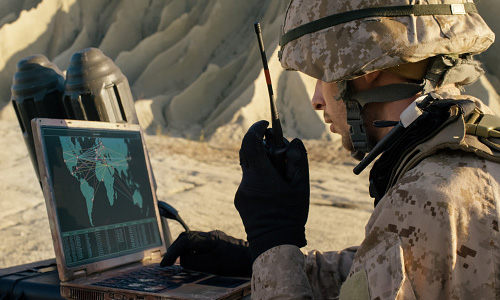 Soldier using laptop computer and radio for communication during military operation in the desert