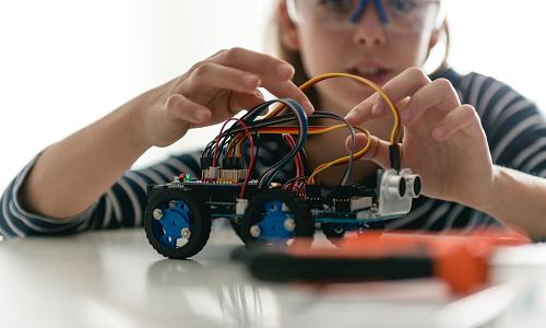 Young girl building robotic car