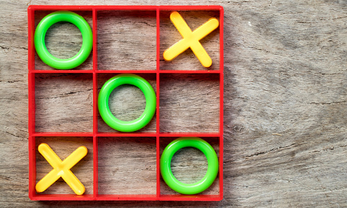 Plastic tic tac toe game on a wooden table