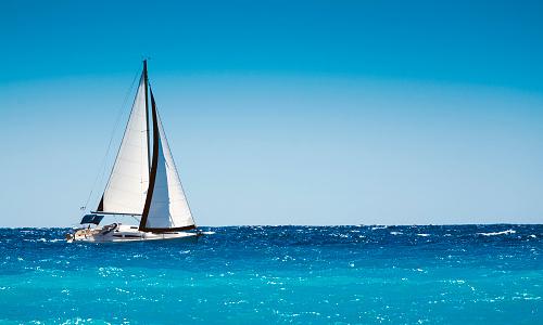 White boat sailing in the open blue sea