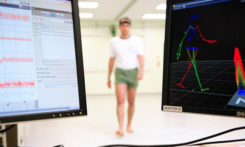 Man main gait being measured by wearable sensor with data being recording on two computers