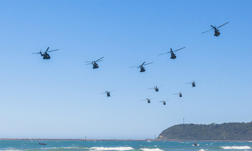 Helicopters flying in formation over ocean