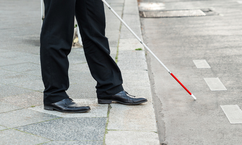 A man standing on a curb with a cane