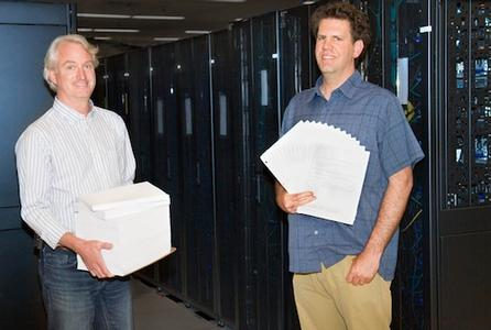 Reid Priedhorsky and Tim Randles hold stacks of papers to illustrate how they hope to streamline code.