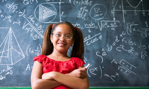 Young Girl Standing in Front of a Chalkboard