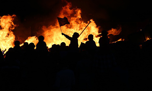 Protesters standing in front of a fire