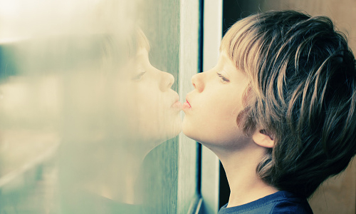 Young boy looking through a window