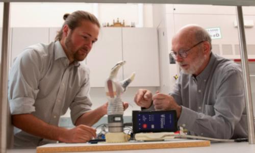 "University of Utah Ph.D. student Jacob George and associate professor Greg Clarke examine the ""LUKE arm"""