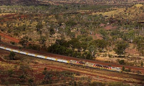 Photo of a train running through mountainous terrain in Australia.