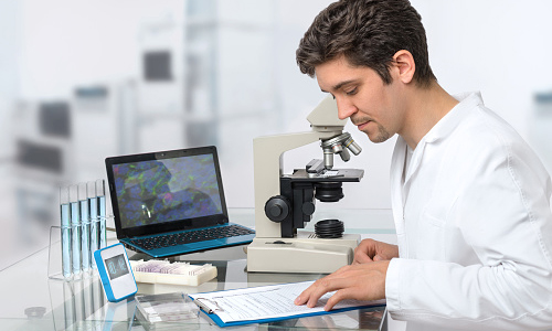 Scientist sitting at a desk with a computer and a microscope
