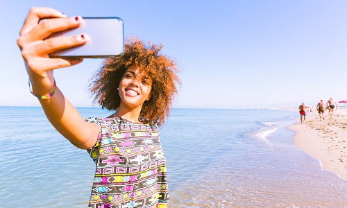 Woman on beach taking selfie with phone