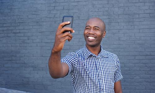 Smiling man takes selfie