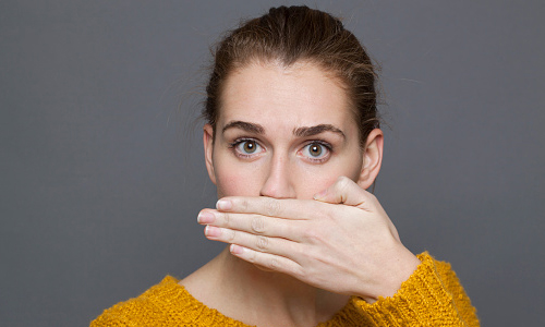 Woman covers her mouth with one hand