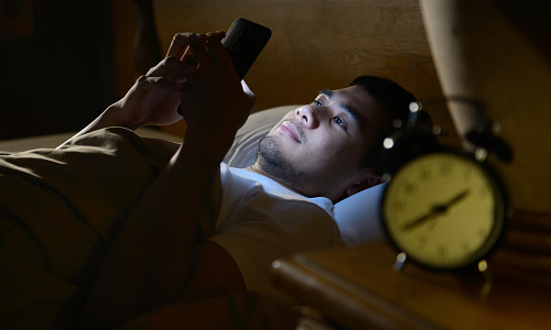 Man using smartphone in bed in the dark
