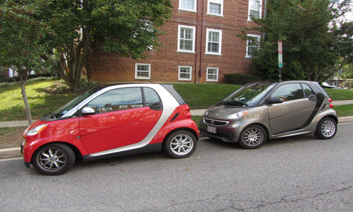 Two smart cars parked on a street