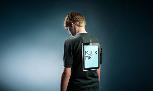 Boy with tablet taped to his back and 'kick me' on tablet screen