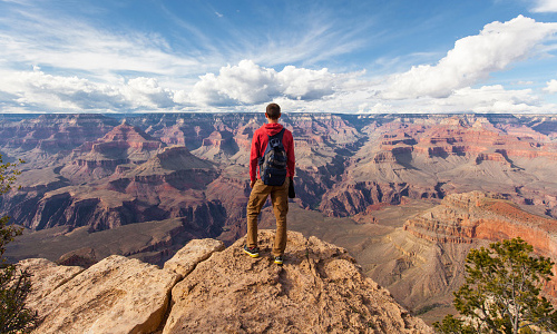 Hiker standing on rock overlooking the grand canyon