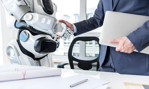Man holding a laptop shaking hands with a robot