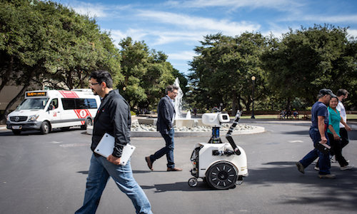 A Stanford computer scientist walking with a robot called JackRabbot at the university.