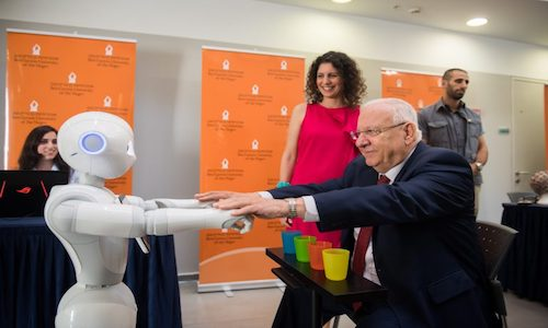 Israel's President Reuven Rivlin stretches arms with robot to demonstrate how it can be used for physical therapy.