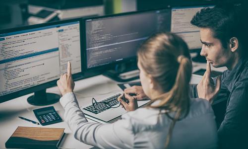 Man and woman looking at computer screens