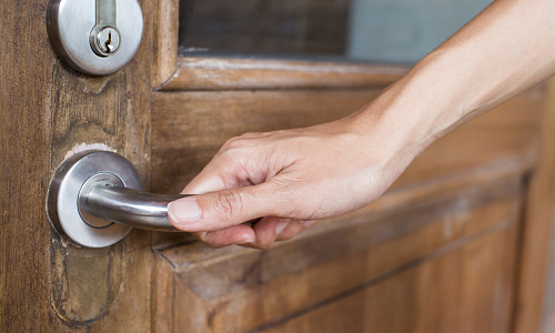 Hand holding doorknob of wooden door