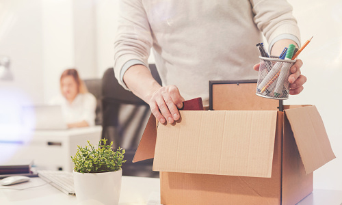 Office worker putting belongings from desk into a box