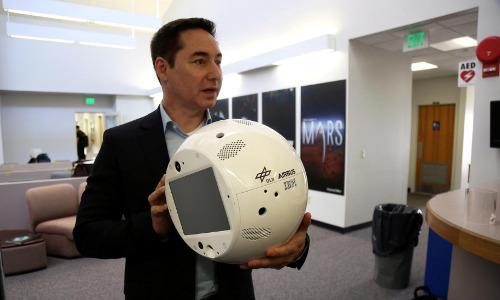 IBM's Bret Greenstein holding clone of the CIMON robot