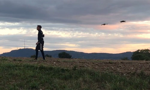 An actor standing in the field with drones in the sky behind him