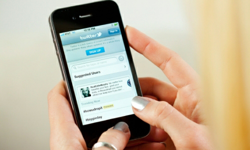 Woman holding cellphone with twitter sign-up page