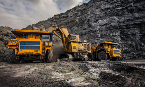 Two mining trucks being loaded with coal