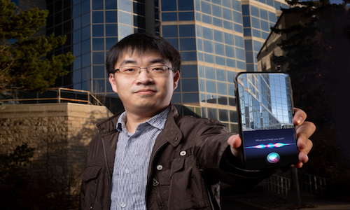 Photo of Hao Zhang holding a smartphone showing apps such as Siri that can run safer, faster and with more energy.